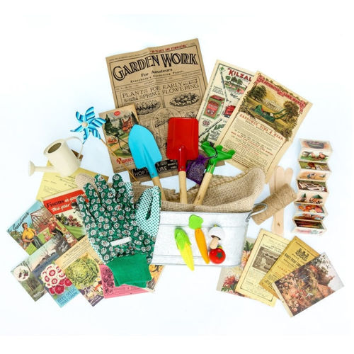 Reminiscence Kit - Garden Delights, up to 14 tactile items to use for reminiscence and discussion in care homes, image shows planter with assorted gloves, seeds, faux vegetables,  watering can and many other items