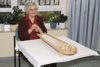 Tabletop Ten Pin Bowling game, eco friendly wooden game in a handy size, natural wood colour with movable chute to direct the balls, image shows elderly lady playing the game in a care home, Set includes:  wooden bowling track 3 x metal balls 10 wooden cones Size: ((l) 86cm x (w) 23cm x (h) 9.5cm.