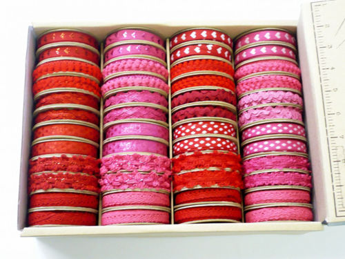 Hanging Ribbon, image shows a box of reels of pink and red assorted ribbon wound on circular spools, length 2m