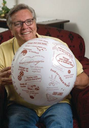 Toss and Talk Ball - All About Men, inflatable ball with printed male-related conversation starters around the outside, questions include 'Military Rankings in the Army' or 'Breeds of Dog', image shows older man seated and holding the ball. Ball has white background and brown text, size: (dia) 60cm.