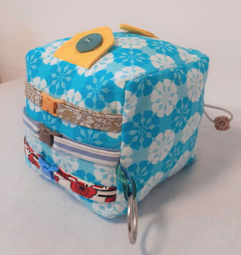 Blue Fidget Cube - Large is hand made and ideal for older care home residents, Mat features:  multicoloured textured fabrics clips lift up flaps ribbon loops zip Hand wash or machine on gently cycle.  Size: (13cm x 13cm)