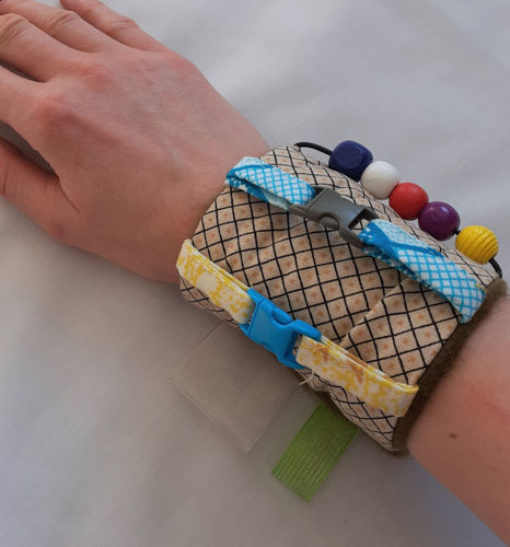 Fidget Arm Band - Fur Lined, tactile fabric arm band for dementia patients, Arm Band features:  textured fabrics soft fur lining buttons clip buckle theading beads velcro fastening Hand wash or machine on gentle cycle.  Size: (23cm x 10cm).